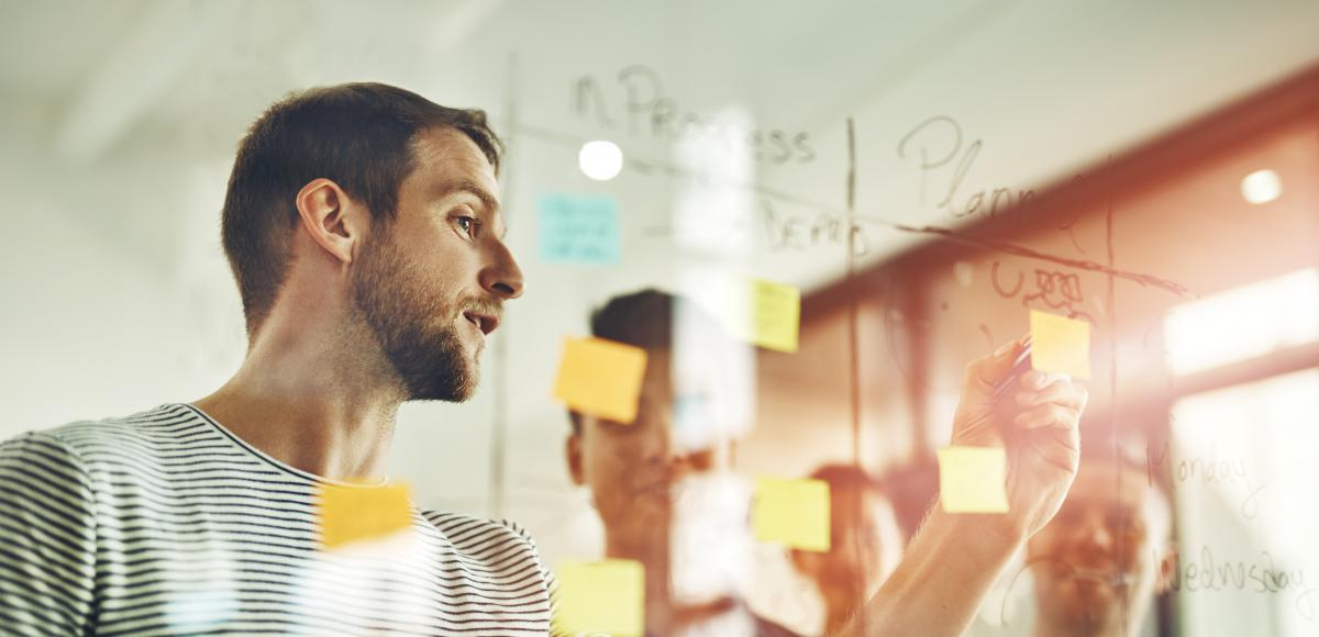 Man consulting others about plans with post-it note