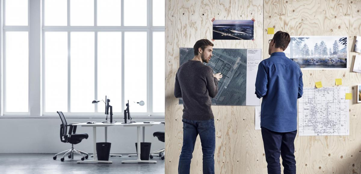 Two men standing in a office discussing technical drawings