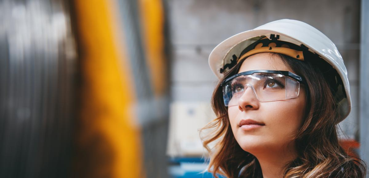 Young businesswoman white helmet googles industrial environment