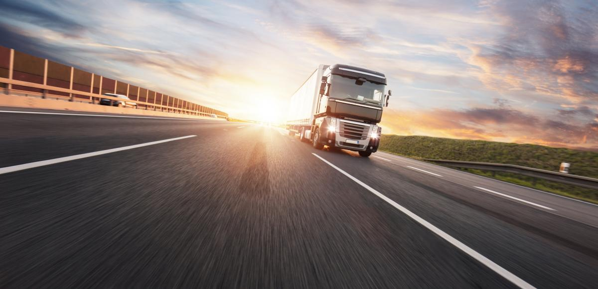 Heavy goods lorry driving along a sunlit road