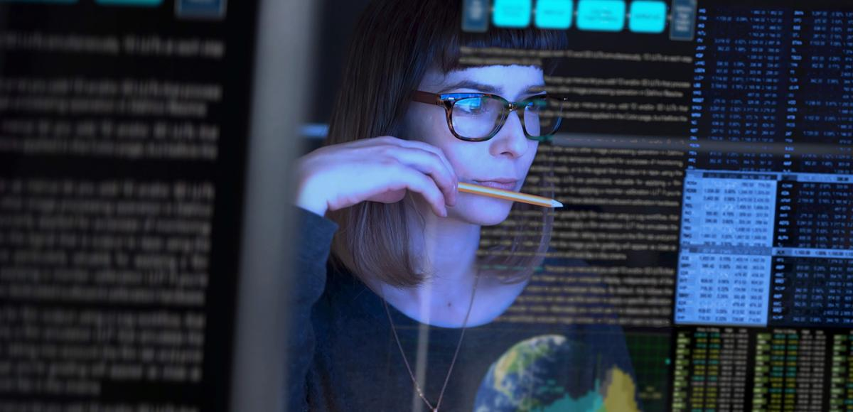 Woman in glasses looking into a computer