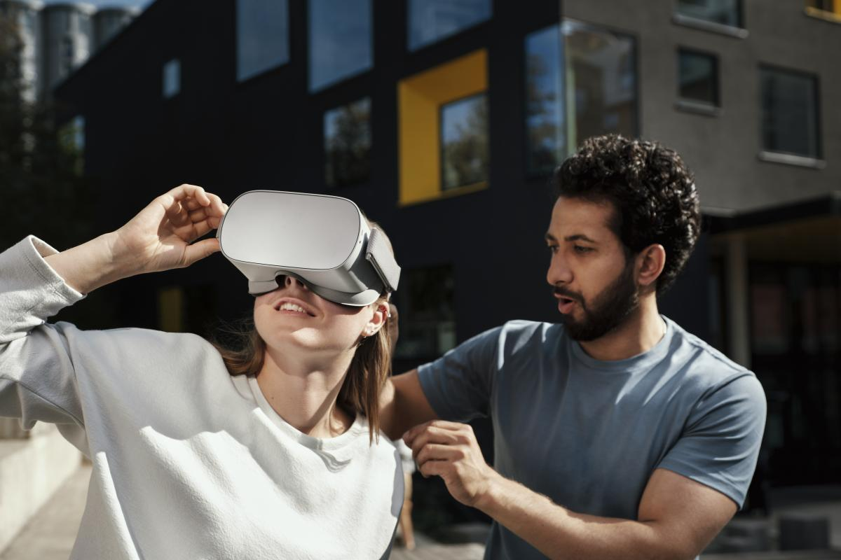 A woman wearing virtual reality headset and a man is helping her.