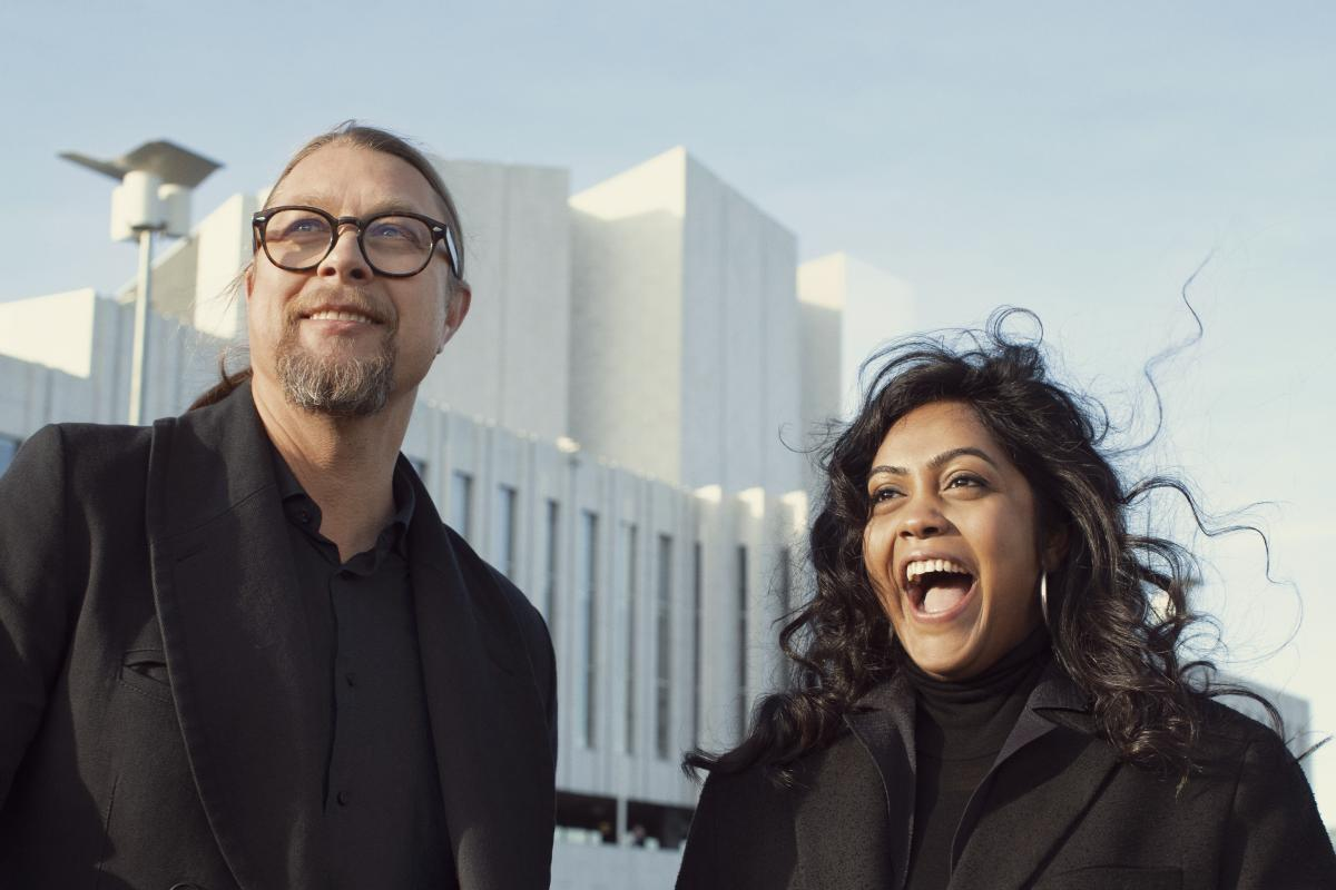 Smiling man with glasses and smiling woman in front of building