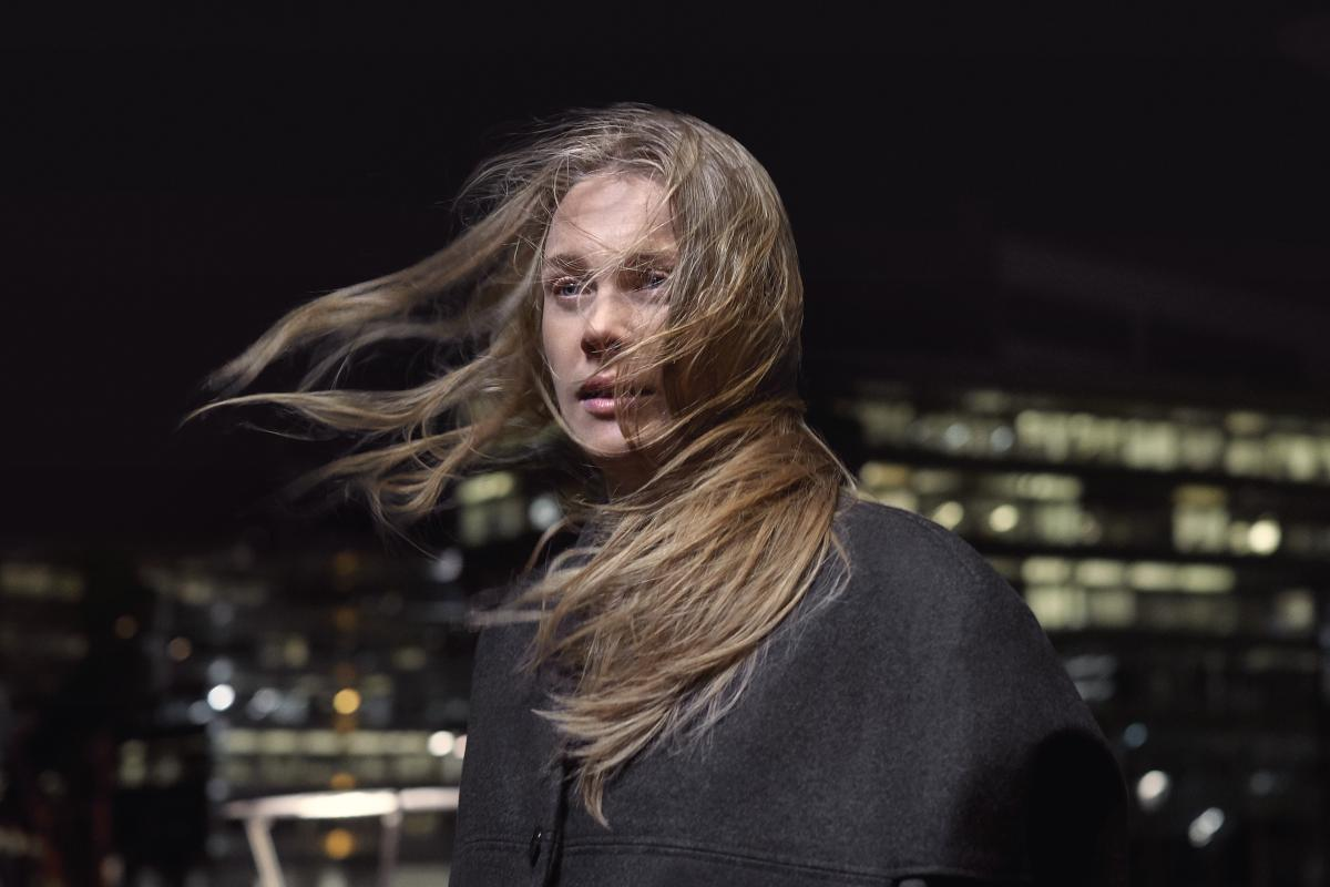 Blonde woman with hair blowing in the wind at night