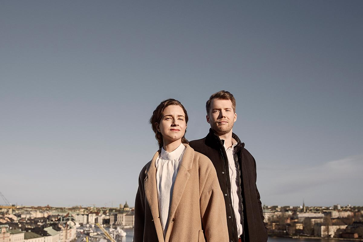A man and a woman standing on a rooftop looking out over the city