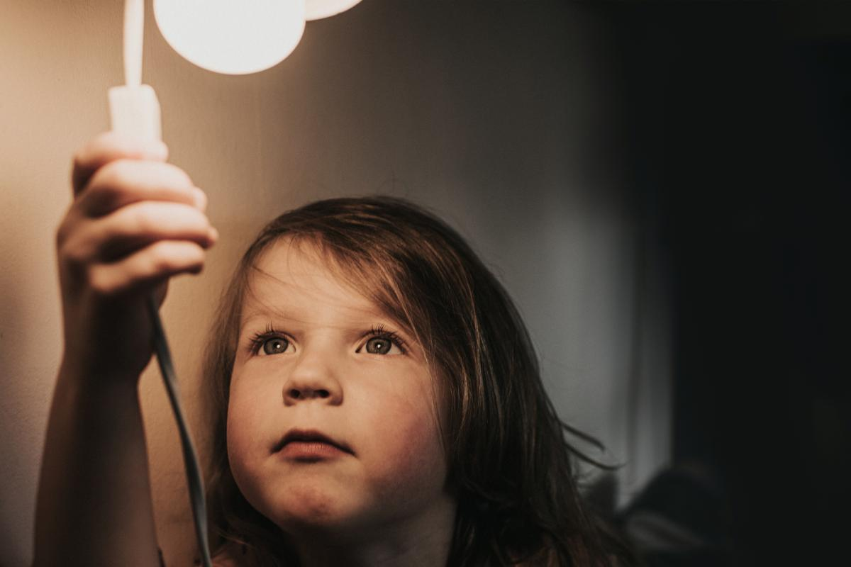 Small child reaching up to switch on light