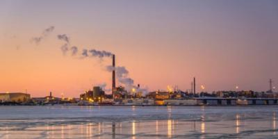 Kotkamills factory for wood recycling with smoke at sunset