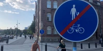 A sign showing that walking and biking is forbidden, and two women riding bikes in the background.