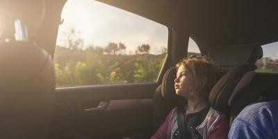 Child in car looking out through window on sunny sky