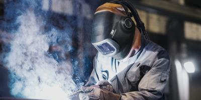 person welding wearing a helmet and creating a cloud