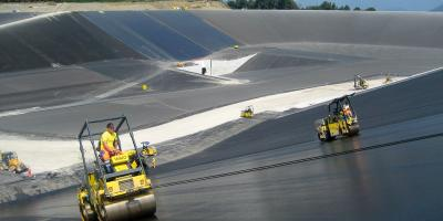 Tandem rolloers lining a reservoir with a layer of asphalt