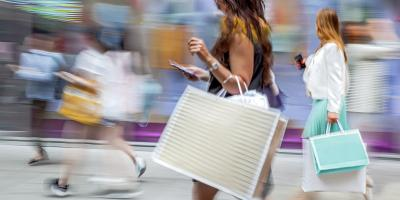 Shoppers walking against a blurry background indicating movement