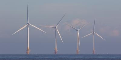 Offshore wind turbines. Green energy. Row of four environmentally friendly wind powered turbines on the sea horizon off the coast of Great Yarmouth UK.