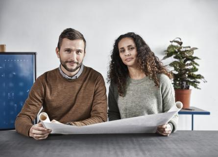 Man and woman looking into the camera holding a technical drawing