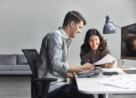 A man and woman reading technical drawings at a desk