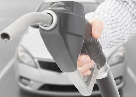 Black color fuel pump gun in hand with white car on background