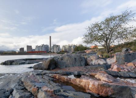 View by the water, rocks in the shore, buildings in the background