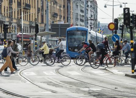People cycling across the street, tram in the background