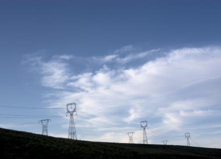 Powerlines on hill against blue sky