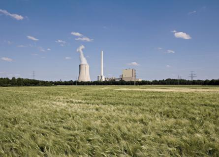 The picture shows a power plant and a grain field.