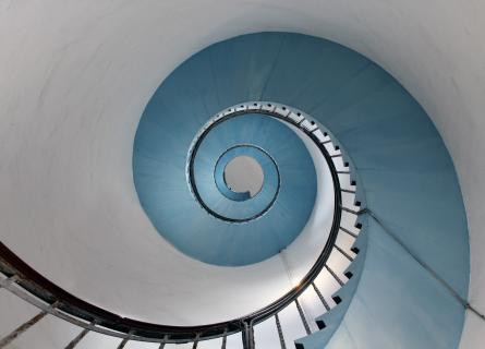 Spiral staircase looking upwards in ice blue and white with cast iron railings