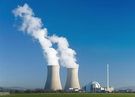 Nuclear power station with two steaming cooling towers in blue sky.