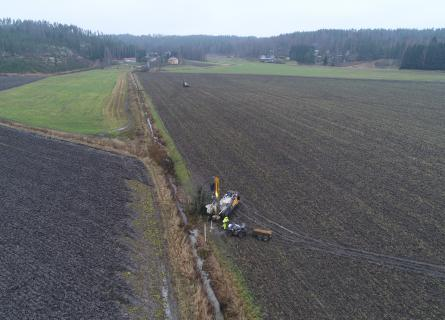 People working with the soil in Finnish field landscape