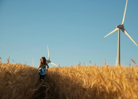 Girl in floral dress is running in corn field with wind turbines