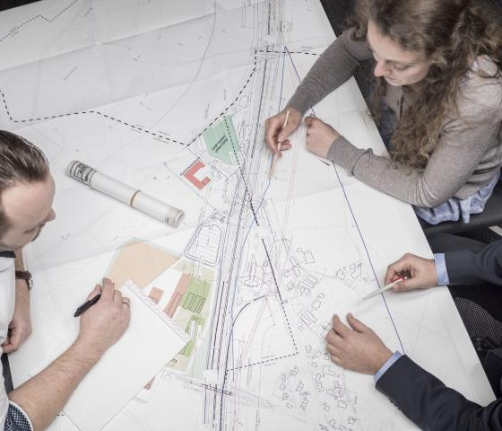 people diskussing developing blueprint on table