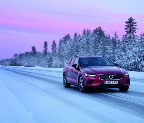 red volvo driving on snowy road
