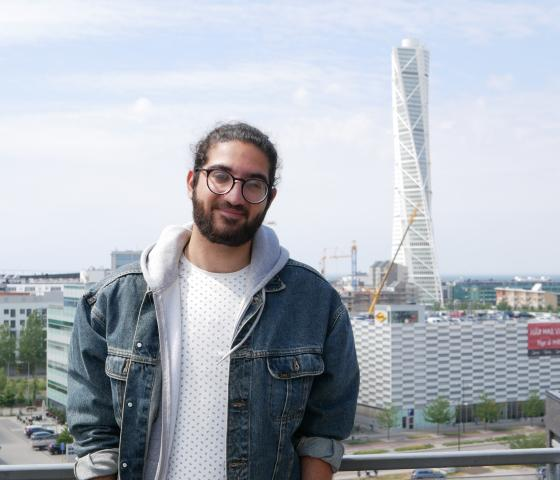 Nima standing in front of Turning Torso in Malmö with his hands in his pockets