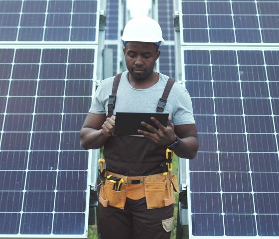 Man in safety gear in front of solar panels
