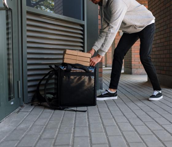 Man packing brown cardboard boxes into a black bag