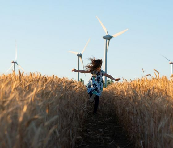 Girl in floral dress running through field towards wind turbines