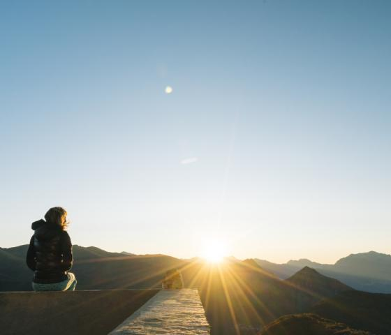Person looking out over sunrise above mountain peaks